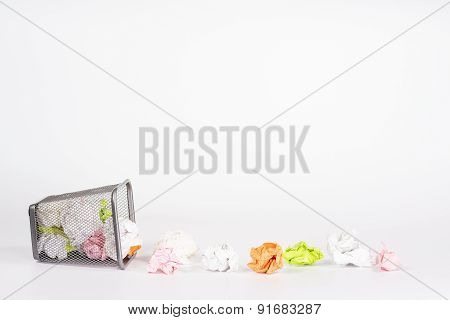 isolated fallen wastebasket full of color paper balls