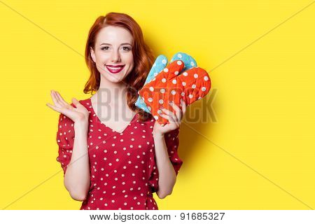 Smiling redhead girl in red polka dot dress and mittens on yellow background. poster