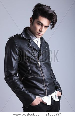 Atrractive young fashion man looking at the camera while holding his hands in pockets.