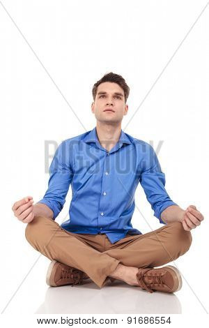 Young casual man sitting in a meditation position with his legs crossed looking up.
