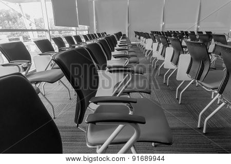 Many chairs arranged neatly in a training room made with black and white color.