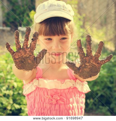 Girl shows her dirty hands. Toned image