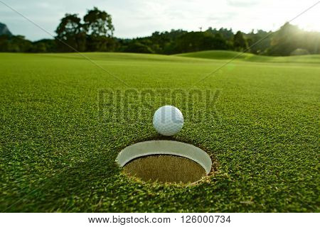 the flare lights photo of white golf ball near hole on fairway with the green background in the country side