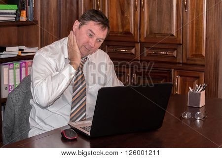 A man in his midlife sits in his study in front of a laptop while rubbing his neck as he stresfully looks at the screen.