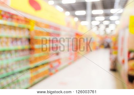 Defocused long brightly lit colorful grocery aisle in a modern hypermarket store