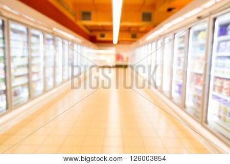 Defocused Brightly Lit Frozen Food Aisle In Modern Supermarket