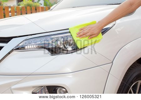 A woman hand with yellow microfiber cloth cleaning big white car, car concept, car idea, car housework, car cleaning , car washer.