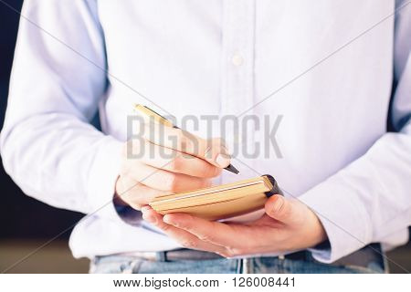 Frontview of male with purple shirt and jeans on writing in notepad