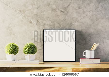 Closeup of wooden table with blank frame two flowerpots iron mug with pencils and book on concrete background. Mock up