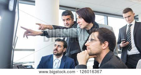 Business team looking at data on multiple computer screens in corporate office. Business people trading online. Business, entrepreneurship and team work concept.