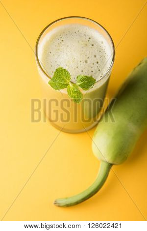 Juice of bottle gourd or lauki juice or Lagenaria siceraria juice, bottle gourd juice, powerful health juice popular in India, isolated over white background