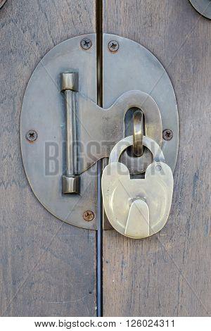 Ancient brass lock on wooden door with handle