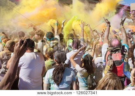 HAMPTON, GA - APRIL 2016:  A large crowd of runners who completed the Color Run toss packets of colored corn starch into the air creating an organic explosion of colors over the group in Hampton GA on April 2 2016 .