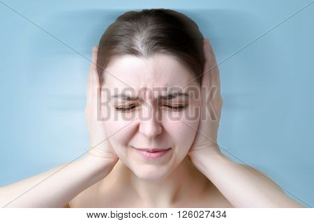 A young woman suffering from noise and covering her ears