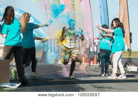HAMPTON, GA - APRIL 2016: A runner gets squirted with multiple colors of corn starch at The Color Run in Hampton GA on April 2 2016.