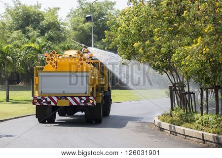 Yellow Water Tanker Watering Trees in a Garden