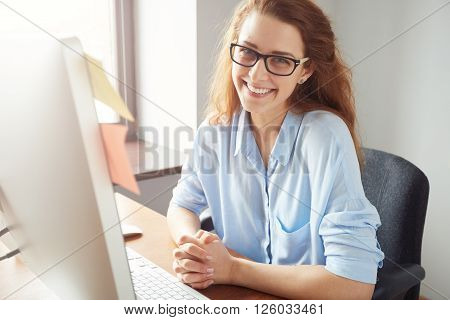 Portrait Of Happy Successful Caucasian Businesswoman In Blue Shirt And Glasses Looking And Smiling A
