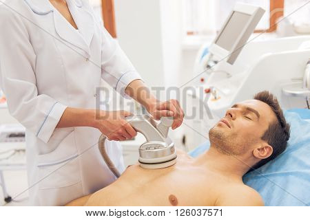 Handsome man is getting skin treatment. Female doctor is undertaking the procedure using a modern equipment