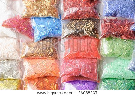 Colorfull glass beads batches in plastic bags for beadwork in craft shop