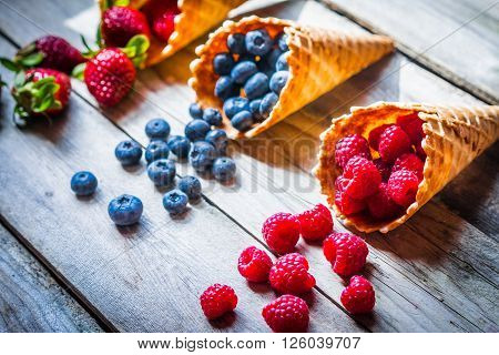 Berries in waffle cones on rustic background