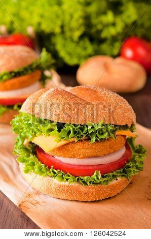Fresh fishburger sandwich on the table. Selective focus in the middle of fishburger