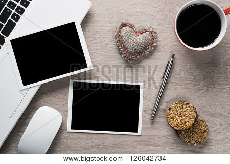 Laptop with coffee cup photos and pen on wooden table