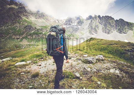 Man Traveler with big backpack hiking Travel Lifestyle concept rocky mountains on background Summer adventure expedition vacations outdoor