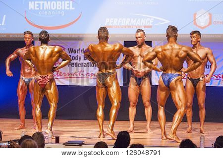 MAASTRICHT THE NETHERLANDS - OCTOBER 25 2015: Male bodybuilders Ali Rezah from Iran with other competitors flex their muscles and show their best physique in a lats spread pose on stage at the World Grandprix Bodybuilding and Fitness of the WBBF-WFF