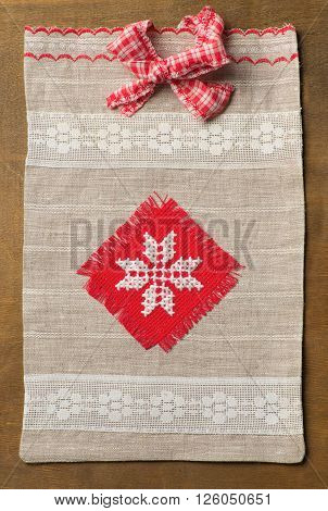 Knitted handmade Gift Bag on wood background