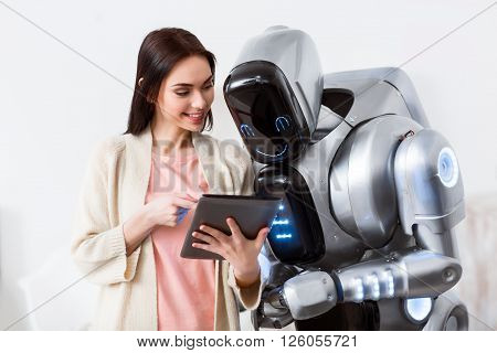 See how it works. Cheerful delighted beautiful girl holding tablet and showing it  to the robot while expressing gladness