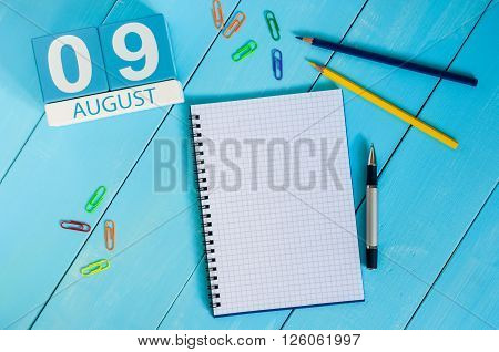 August 9th. Image of august 9 wooden color calendar on blue background. Summer day. Empty space for text.