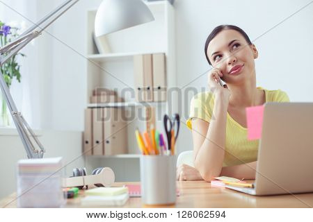Beautiful businesswoman is using a mobile phone for communication. She is sitting at desk in her office. The lady is smiling and looking up pensively