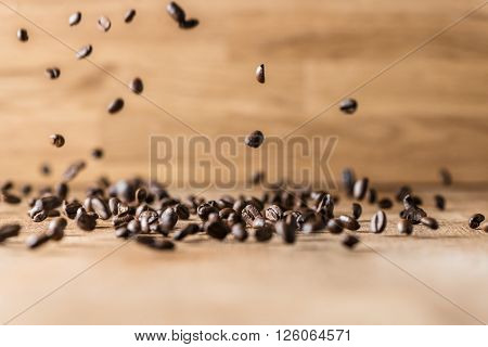 flying roasted brown coffee beans flying on wood background
