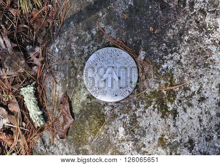 An Appalachian Trail survey marker embedded into rock within Falls Village Connecticut.