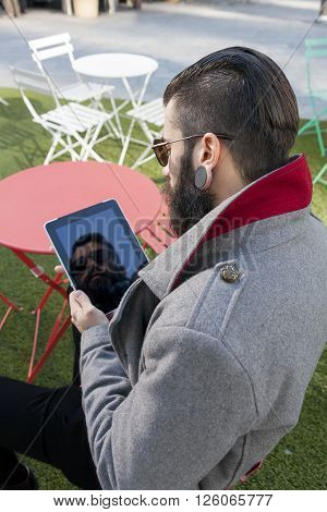 Young Hipster Consults His Laptop Sitting At Bar