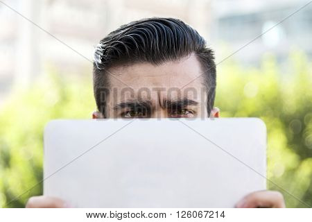 Young Hipster Businessman Holding The Laptop In Front Of Face