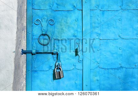 Grunge metal turquoise door with rivets plates and aged metal door handle in the form of stylized lily. Architectural background.
