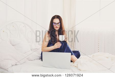 Middle aged woman with laptop in white bed. Woman in eyeglasses looks into gadget pc. Morning coffee. Beautiful woman in blue nightwear at bed surfing internet at her computer. High key. Soft tone