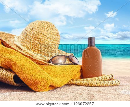 Suntan lotion, straw hat with towel at the beach