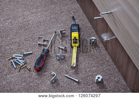 Metal fittings clamps and hand tools for installing furniture.