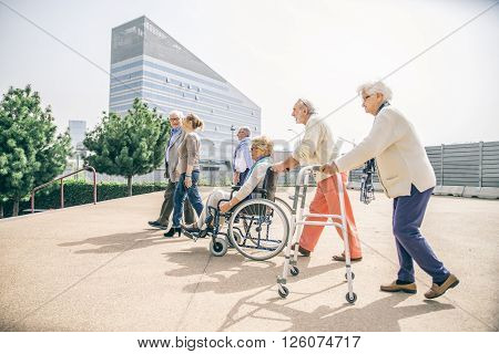 Group of senior people with some diseases walking outdoors - Mature group of friends spending thier time together