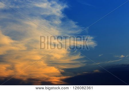 Cloudy sky in sunset light with orange and blue color