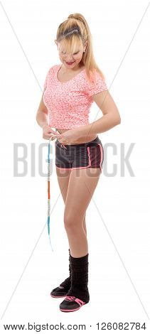 Beautiful woman measuring her waist with a measuring tape over white background