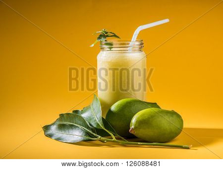 Aam Panna or Salted Green Mano Juice or green kairi panha or kairi pahna, refreshing cold dring in indian summer, over yellow background