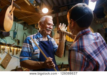 Small family business and traditions: old grandpa with grandson in lute maker shop. The senior artisan gives five to the boy who helps him to make a handmade music instrument