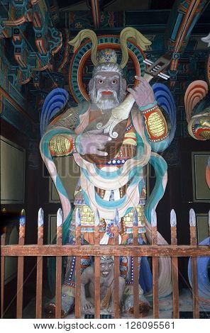 GYEONGJU CITY, NORTH GYEONGSANG PROVINCE / KOREA - CIRCA 1987: A large sculpture of a bearded man playing a lute stands behind a picket fence inside the Bulguksa Buddhist Temple.