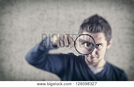 The young man playing with a magnifying glass