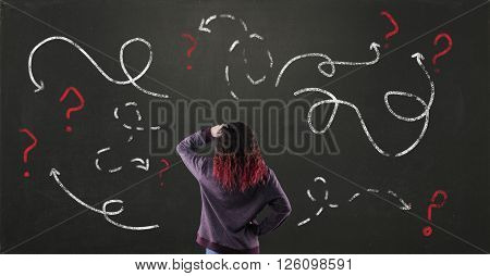 Confused young girl with blackboard drawing different directions and question mark