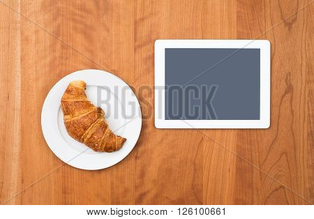 Croissant With Tablet Pc On Wooden Table From Above