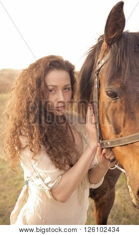 Beautiful girl with a horse outdoors in the countryside.
